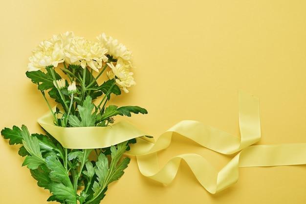 Gele chrysanten bloemen boeket met mooi breed lint op gele achtergrond. wenskaartsjabloon met kopie ruimte