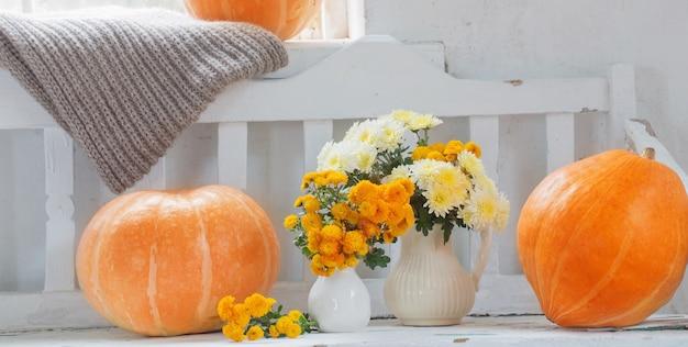 Gele chrysanten in kruik en oranje pompoenen op oude witte houten bank