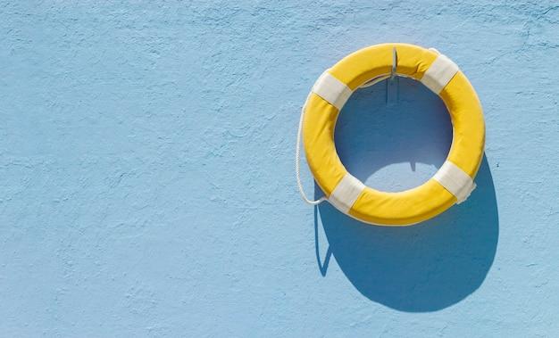 Gele cirkelreddingsboei die op blauwe muur met exemplaarruimte hangt