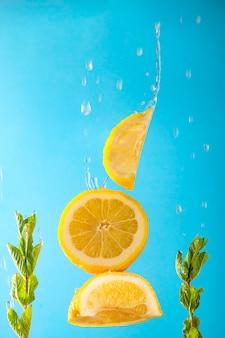Gele citroen en groene munt tijdens de vlucht met druppels sap