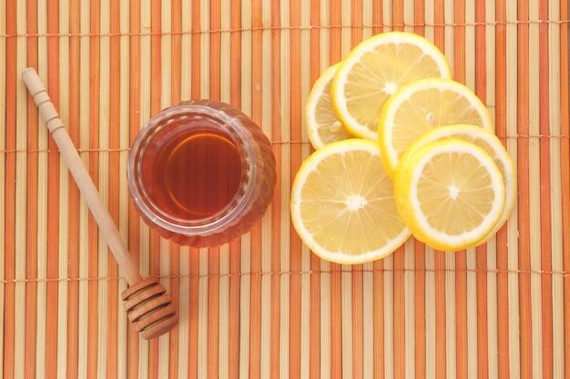 Gele citroen en honing op tafel