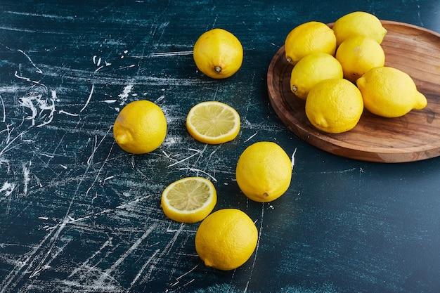Gele citroen en plakjes op blauwe achtergrond in een houten schotel.