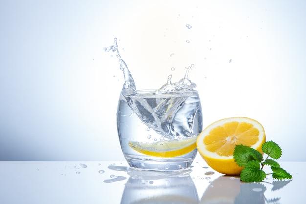 Gele citroenen in een glas en spatten van water. lekker en gezond eten. seizoensgebonden drankjes