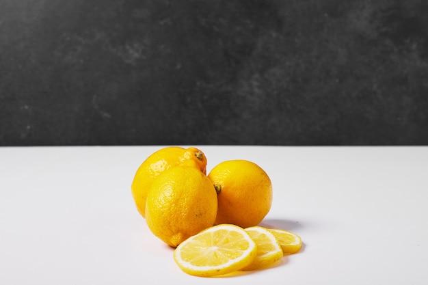 Gele citroenen op wit.