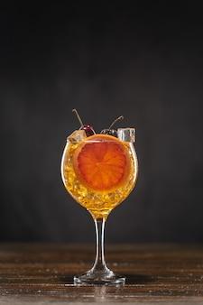 Gele cocktail met kers in een glas staande op een houten tafel, versierd met een schijfje grapefruit