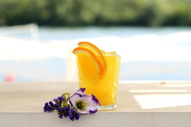 Gele cocktail met sinaasappel, limoen en ijs in een glazen tuimelaar
