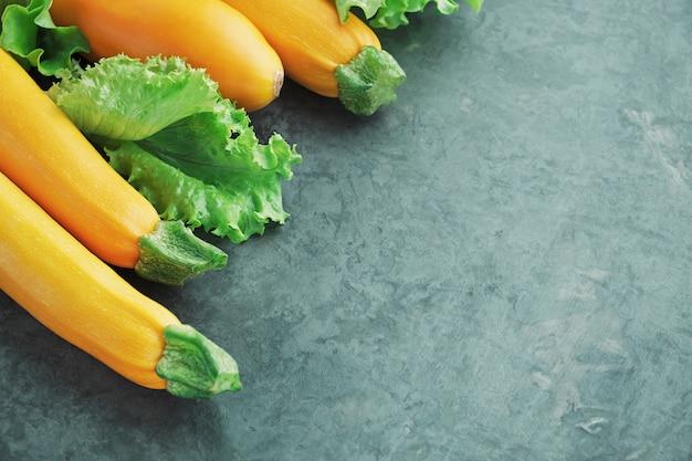 Gele courgette en sla op keukentafel