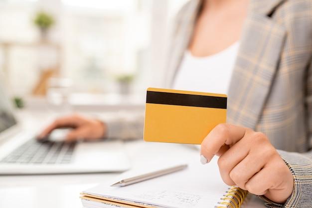 Gele creditcard met zwarte magneetlijn die tijdens het werk door jonge hedendaagse onderneemster op pagina van notitieboekje wordt gehouden