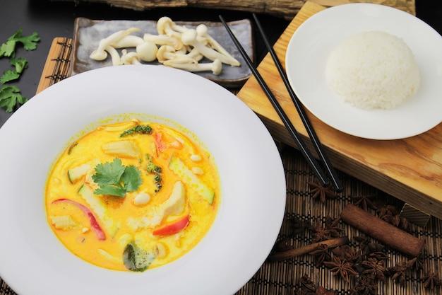 Gele curry met kip op een groot wit bord, rijst en eetstokjes