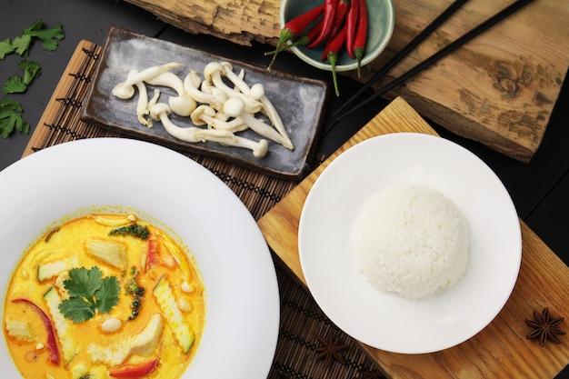 Gele curry met kip op een grote witte plaat, rijst en eetstokjes, bovenaanzicht