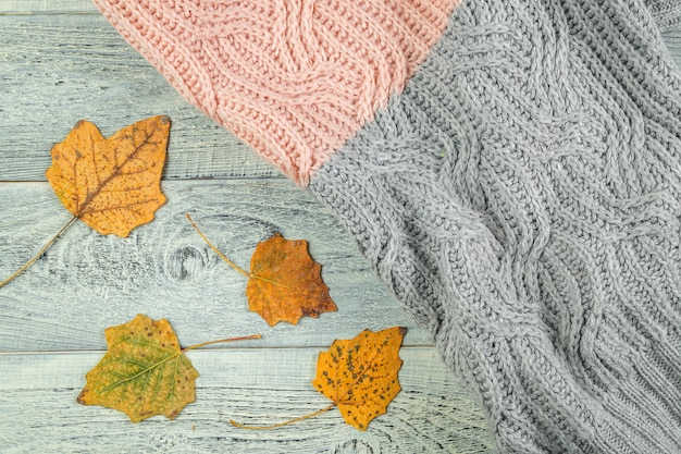 Gele de herfstbladeren op een oude geweven houten achtergrond met een geweven jasje