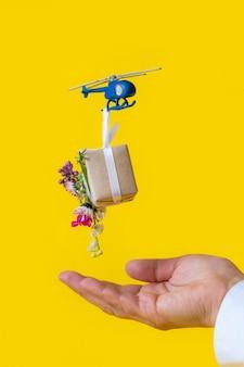 Gele document vakje giftstuk speelgoed de hand van de leveringshelikopter bloemen als achtergrond