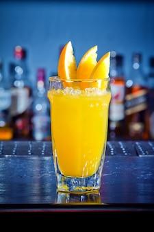 Gele drankcocktail met stukjes sinaasappel aan de toog.