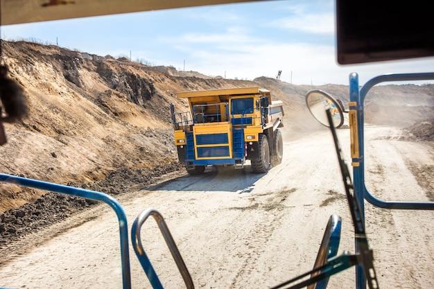 Gele dumper die zich in een kolenmijn beweegt. uitzicht vanaf een andere vrachtwagen
