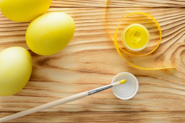 Gele eieren met een penseel en verf op een houten tafel.