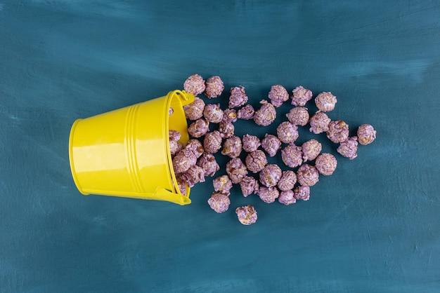Gele emmer met popcornsuikergoed dat over op blauw wordt gemorst