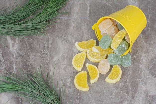 Gele emmer met suikermarmelade op marmeren achtergrond.