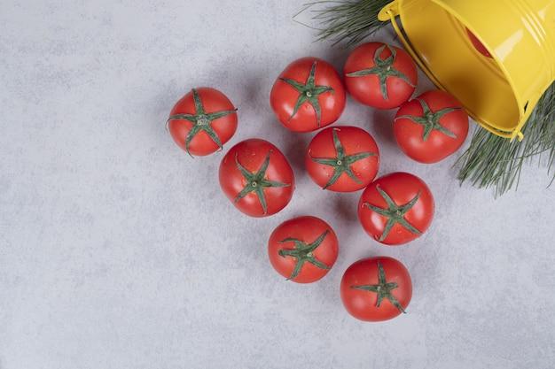 Gele emmer met tomaten op donkere achtergrond