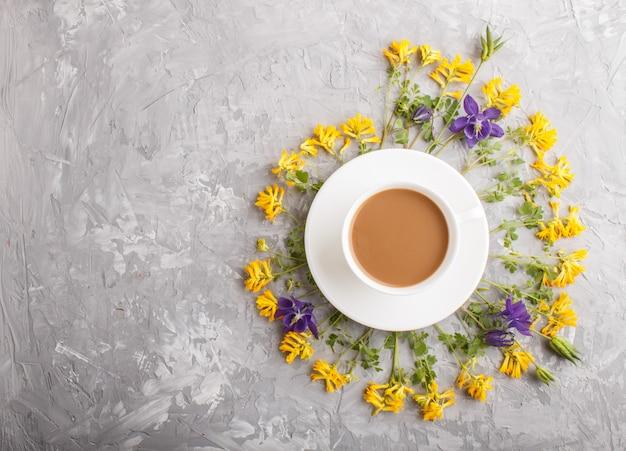 Gele en blauwe bloemen in een spiraal en een kopje koffie op een grijs beton