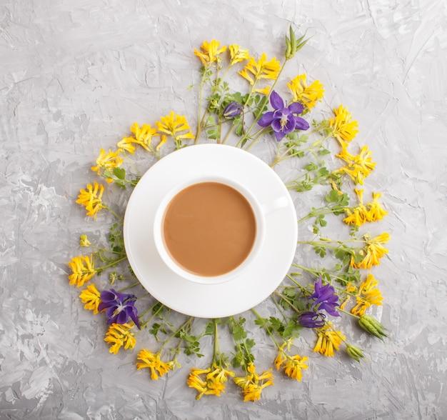 Gele en blauwe bloemen in een spiraal en een kopje koffie op een grijze concrete achtergrond