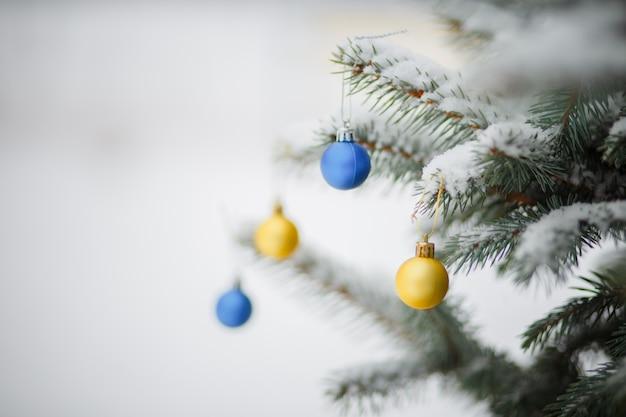 Gele en blauwe kerstboomballen. speelgoed op besneeuwde kerstboom. kerst achtergrond. eerste sneeuwval.