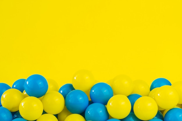 Gele en blauwe plastic ballen in pool van speelkamer