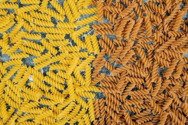 Gele en bruine rauwe fusilli pasta op blauwe ruimte.