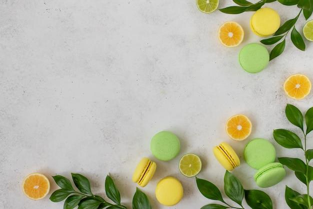 Gele en groene macarons, plakjes citroen, limoen, groene takken.