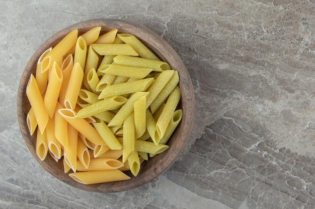 Gele en groene penne pasta in houten kom