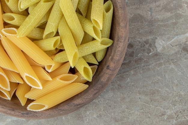 Gele en groene penne pasta in houten kom.