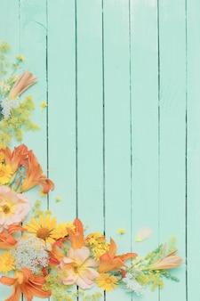 Gele en oranje bloemen op groene houten achtergrond