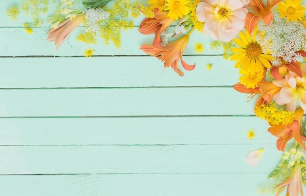 Gele en oranje bloemen op groene houten oppervlak