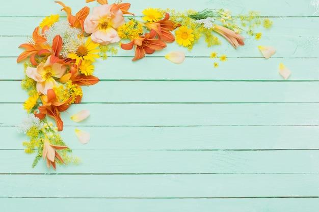 Gele en oranje bloemen op groene houten