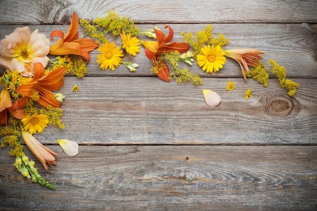 Gele en oranje bloemen op oude houten