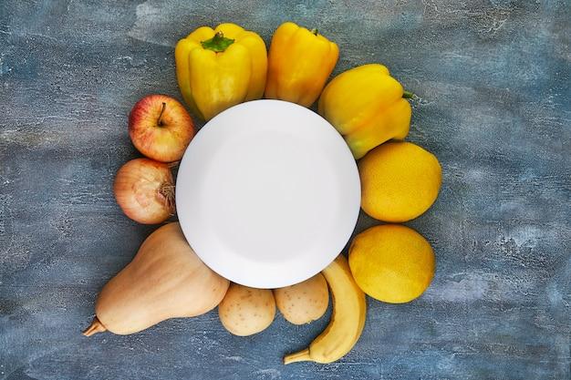 Gele en oranje groenten en fruit zijn ingedeeld in een cirkel op een blauw. uitzicht van boven. gezond eten . plaats voor een inscriptie in een witte cirkel