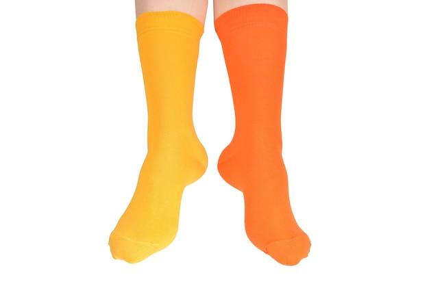 Gele en oranje sokken op vrouwenvoet die op witte achtergrond wordt geïsoleerd.
