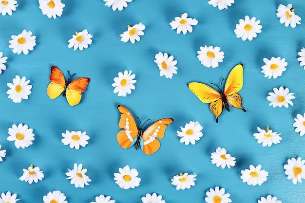 Gele en oranje vlinders en madeliefjes op blauwe achtergrond. bovenaanzicht. zomer achtergrond. plat leggen.