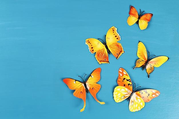 Gele en oranje vlinders op blauwe achtergrond. bovenaanzicht. zomer achtergrond. plat leggen.