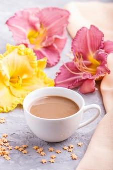 Gele en paarse daglelies met een kopje koffie