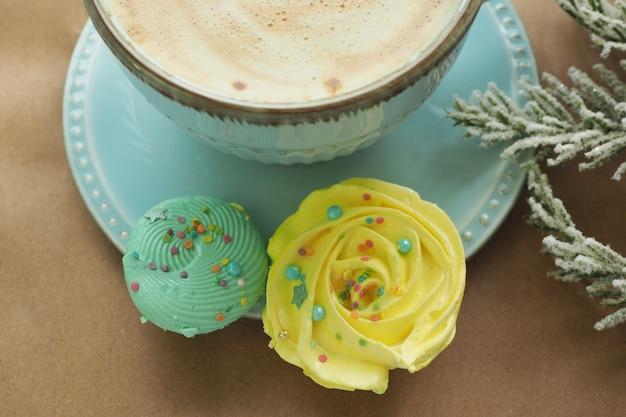 Gele en pepermuntschuimgebakjes bij een kopje koffie. vuren kunstmatige tak