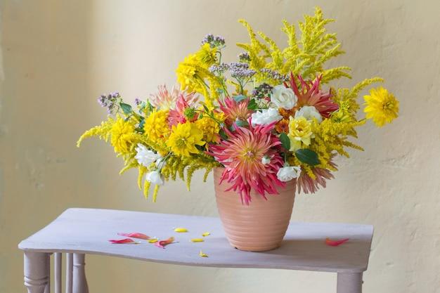 Gele en rode bloemen in vaas op vintage plank
