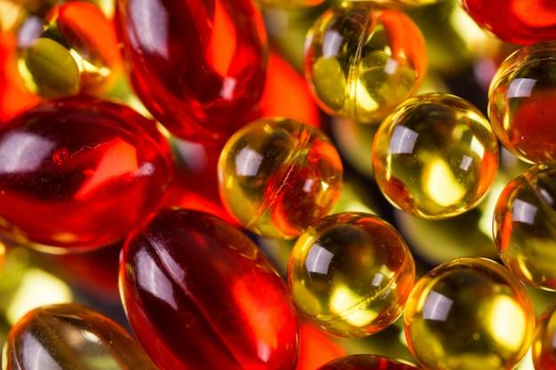 Gele en rode medische capsules op een spiegeloppervlak