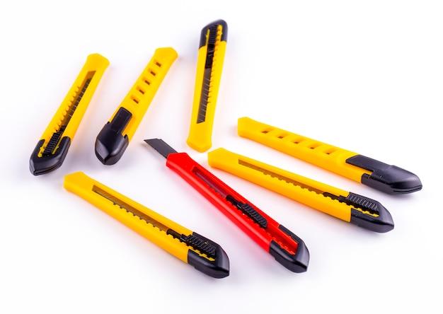 Gele en rode papiersnijder op het wit