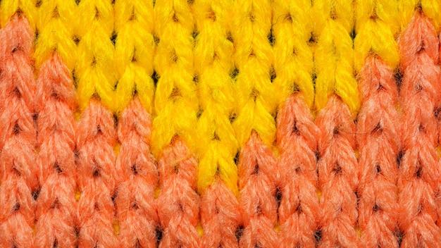 Gele en rode synthetische gebreide stof close-up. gebreide stof textuur achtergrond