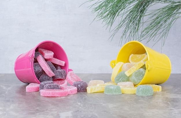 Gele en roze emmers met suikermarmelade op marmeren achtergrond.