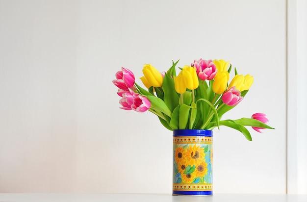 Gele en roze tulpen in een vaas. heldere vakantie achtergrond.