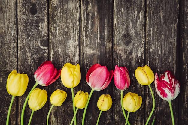 Gele en roze tulpen op grijze houten sjofele lijst