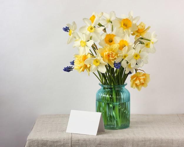 Gele en witte narcissen en een lege witte kaart.