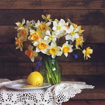 Gele en witte narcissen van verschillende soorten in een glazen vaas