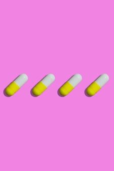 Gele en witte pillen op een roze bovenaanzicht als achtergrond